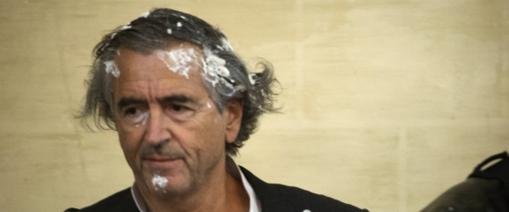 "French philosopher and writer Bernard-Henri Levy looks on after being hit by a cream pie thrown by Belgian notorious pie thrower Noel Godin ahead of a discussion between Belgian artist Jan Fabre and Bernard-Henri Levy on the exhibition ""Facing time. Rops/ Fabre"" in Namur, on May 30 2015. AFP PHOTO / BELGA PHOTO / ANTHONY DEHEZ **BELGIUM OUT**"